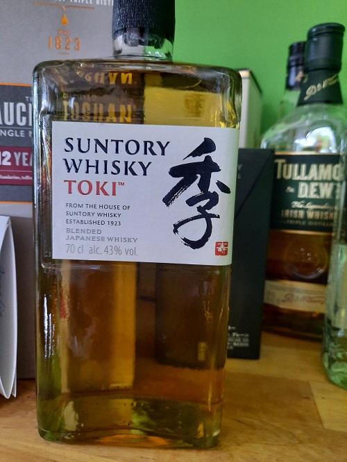 Eine Flasche Suntory Toki im Vordergrund vor anderen Flaschen.
